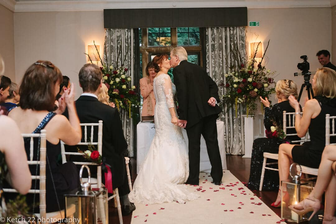 older bride and groom kissing at wedding ceremony