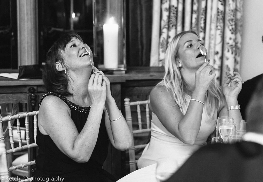 Wedding guests balance spoons on their nose
