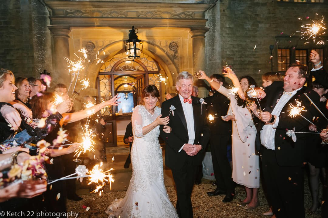 Bride and groom walking through a blaze of sparklers at Foxhill Manor Wedding