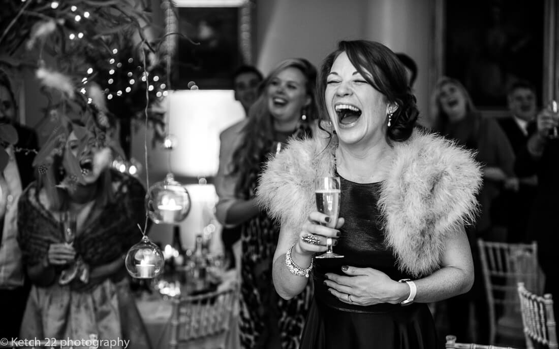 Bridesmaid laughing at speeches at wedding