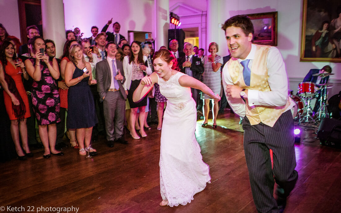 Bride and groom at first dance with cheering wedding guests