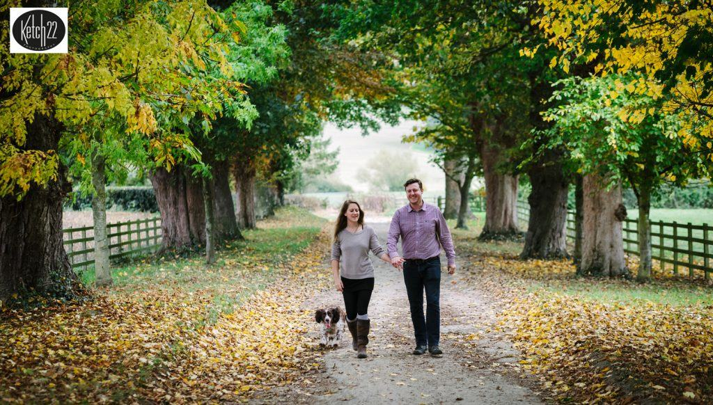 engaged couple walking in countryside with their dog for pre wedding shoot in The west midlands