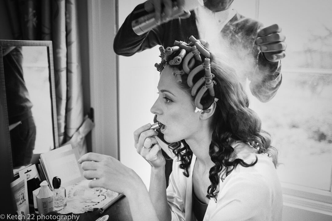 Bride having hairspray applied at wedding preparations
