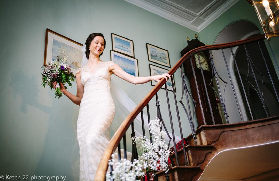 Bride walking downstairs holding flowers at Homme House wedding