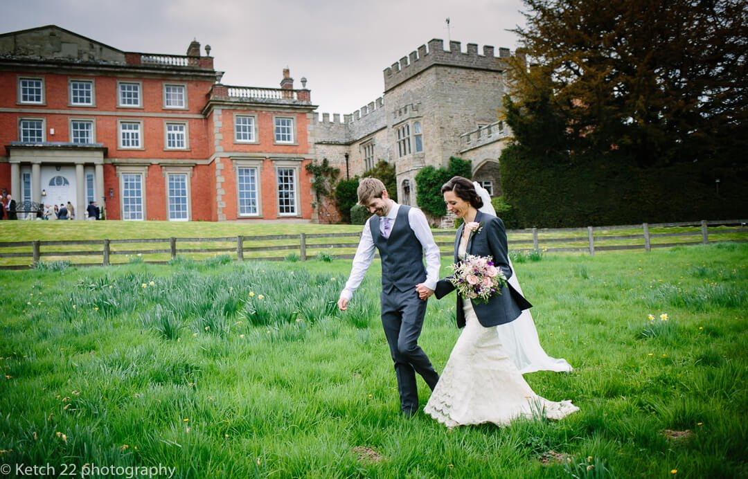 Bride and groom walking in front of recommended wedding venue, Homme House in Herefordshire