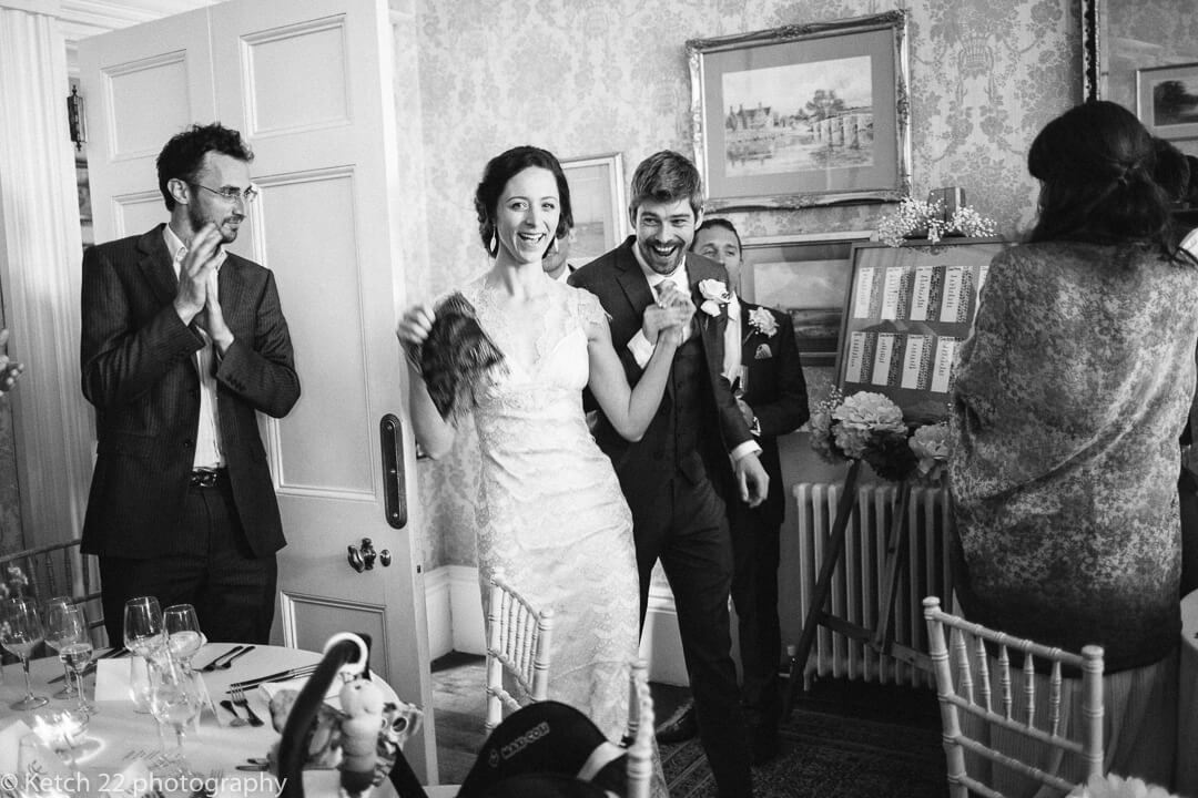 Excited bride and groom enter wedding dinning room at country house wedding