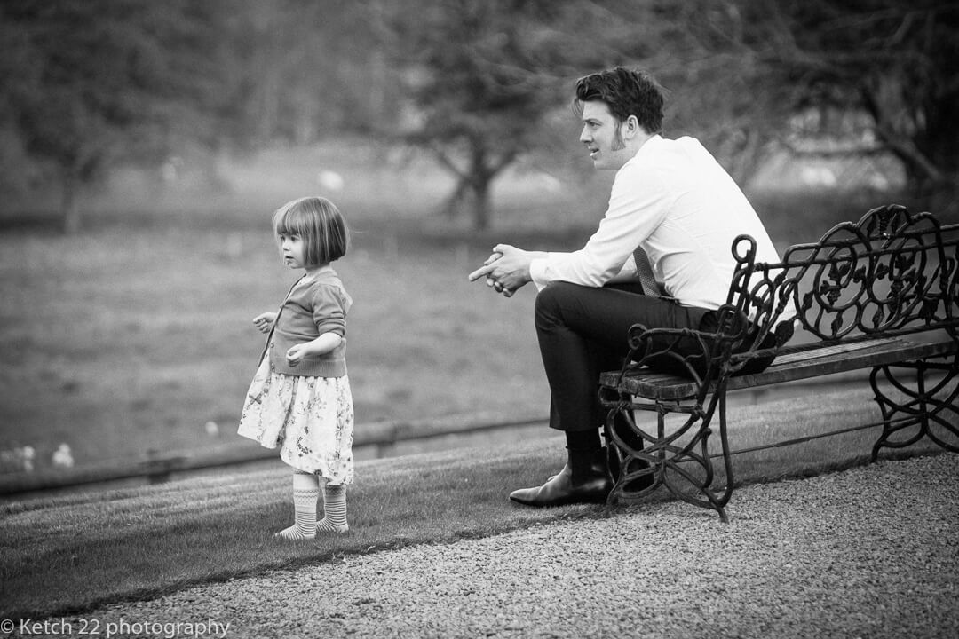 Documentary wedding photo of father and daughter relaxing in garden at wedding