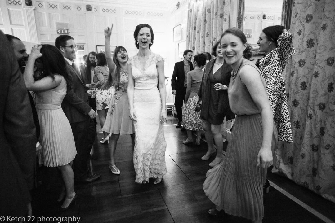 Bride and wedding guests dancing at reception