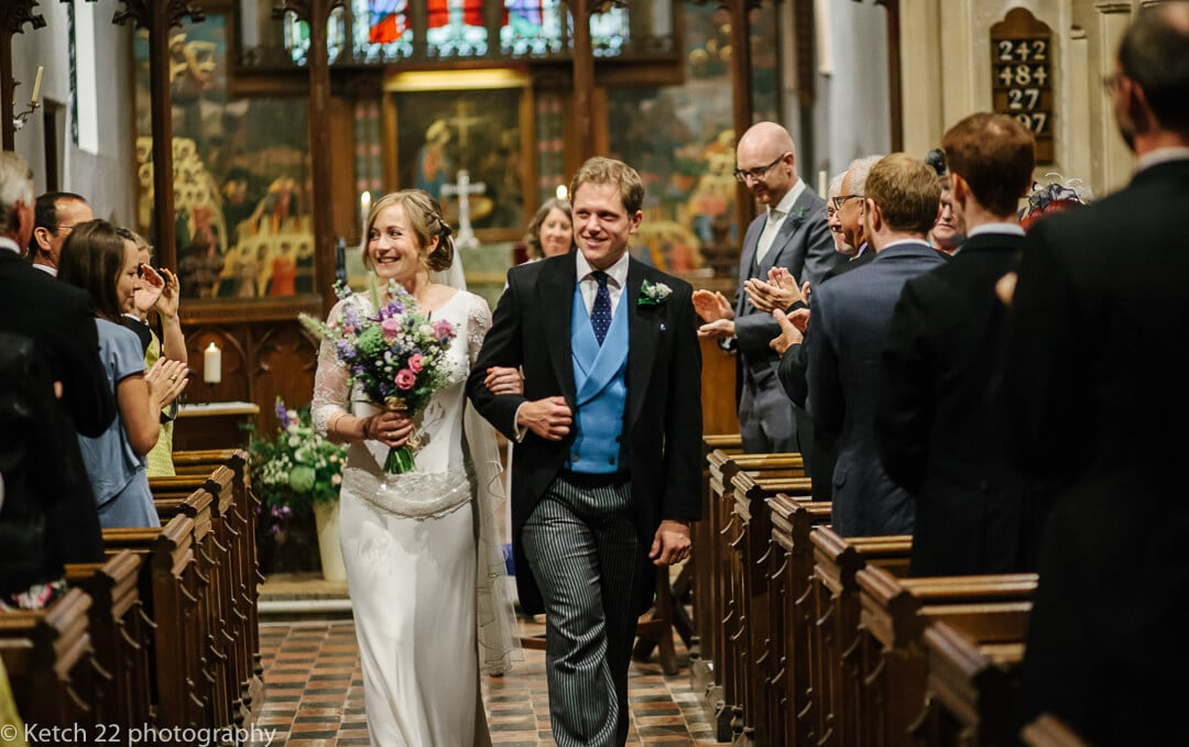 Bride with flowers and groom wearing blue waist coat leaving church