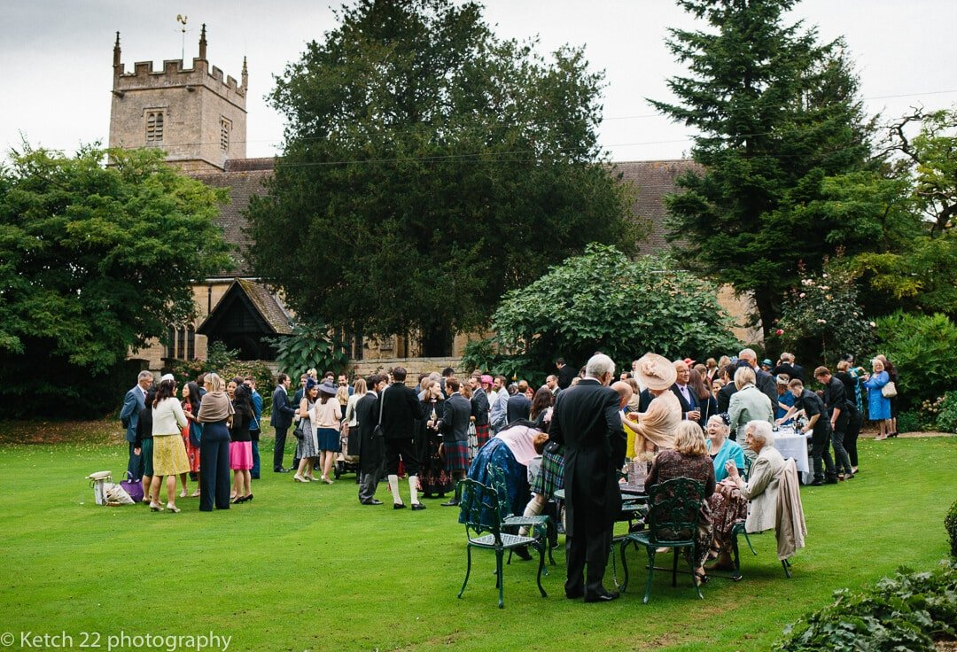 Wedding guests enjoy canapes and drinks on the lawn at Upper Court