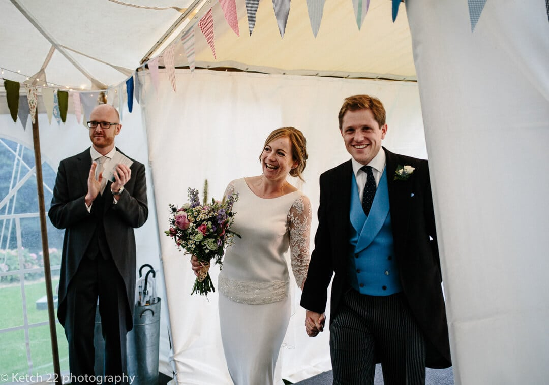 Bride and groom enter wedding marquee