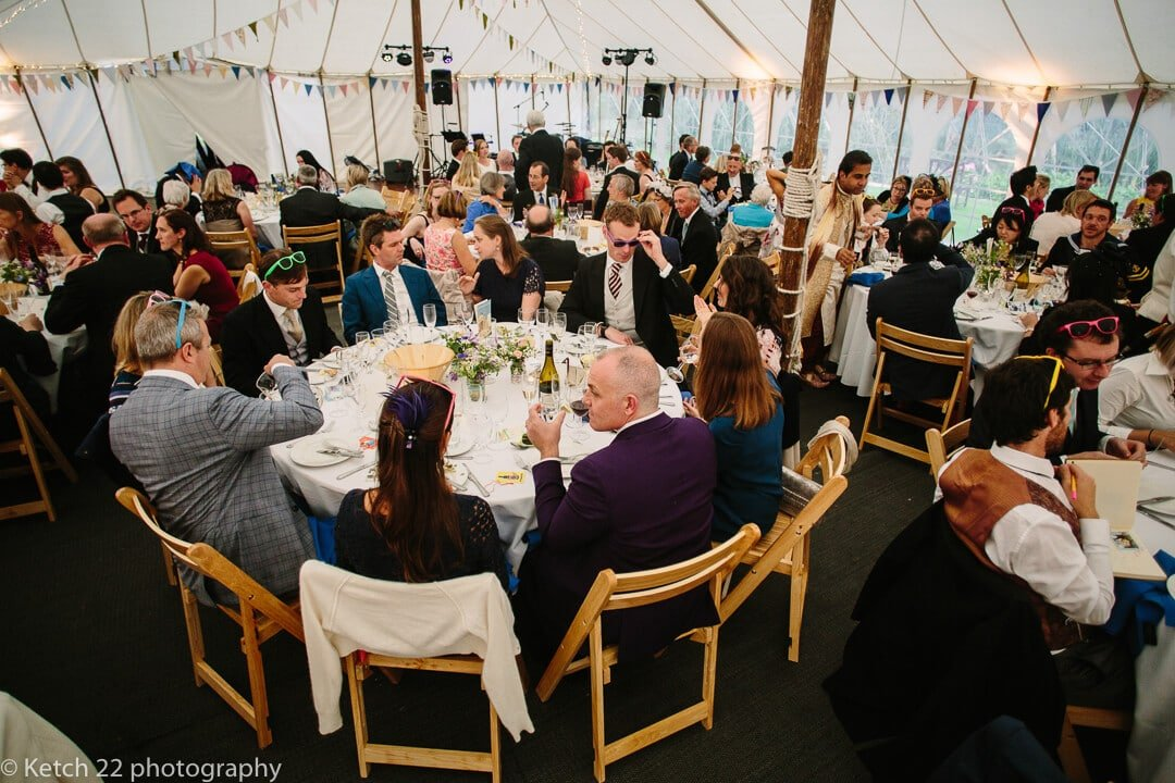 Wedding guests enjoying dinner in marquee