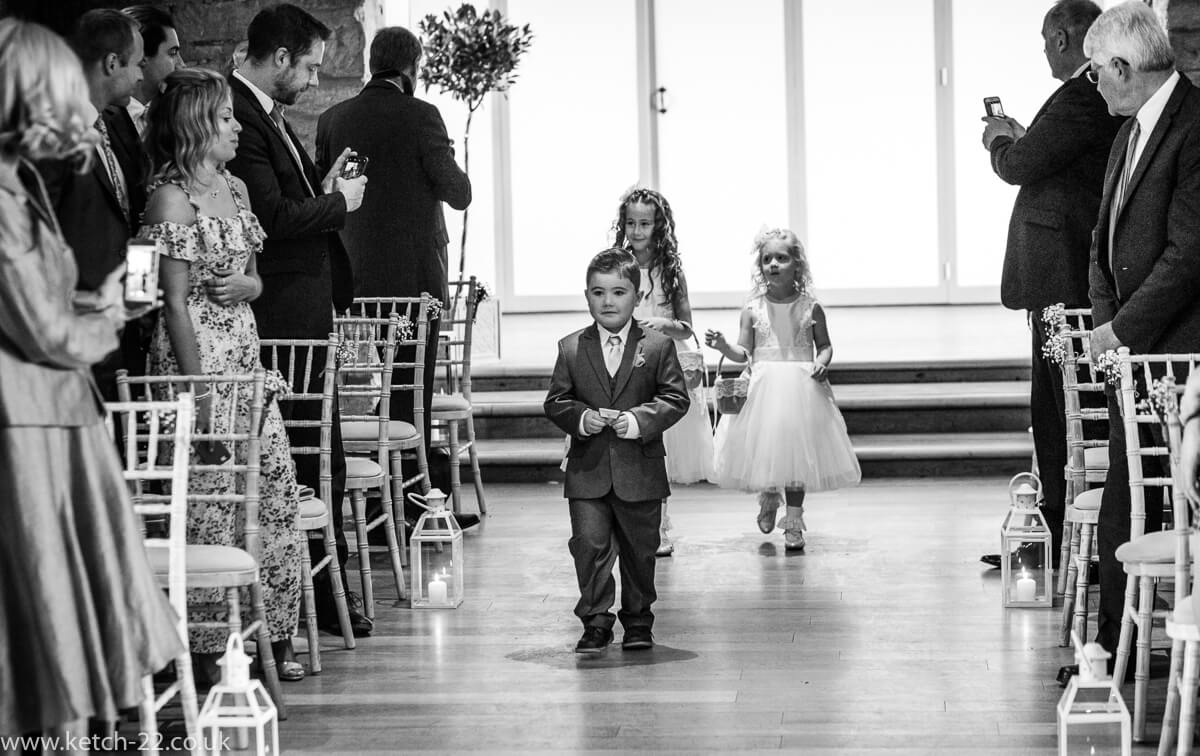 Page boy and flower girls enter wedding ceremony at The Great Tythe Barn in Gloucestershire