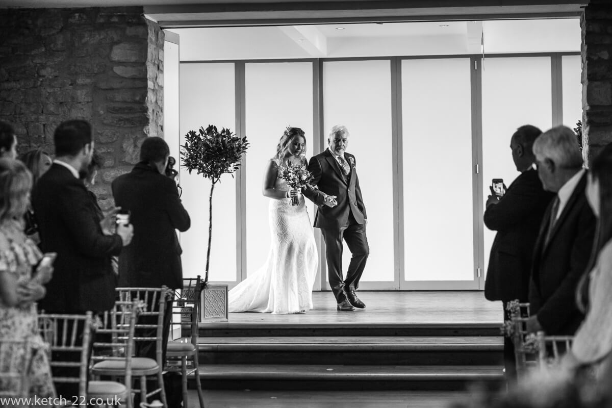 Father of bride and bride enter ceremony at weddings at The Great Tythe Barn