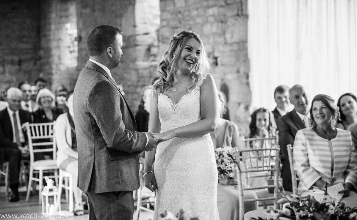 Bride laughing during the vows at the Great Tythe Barn