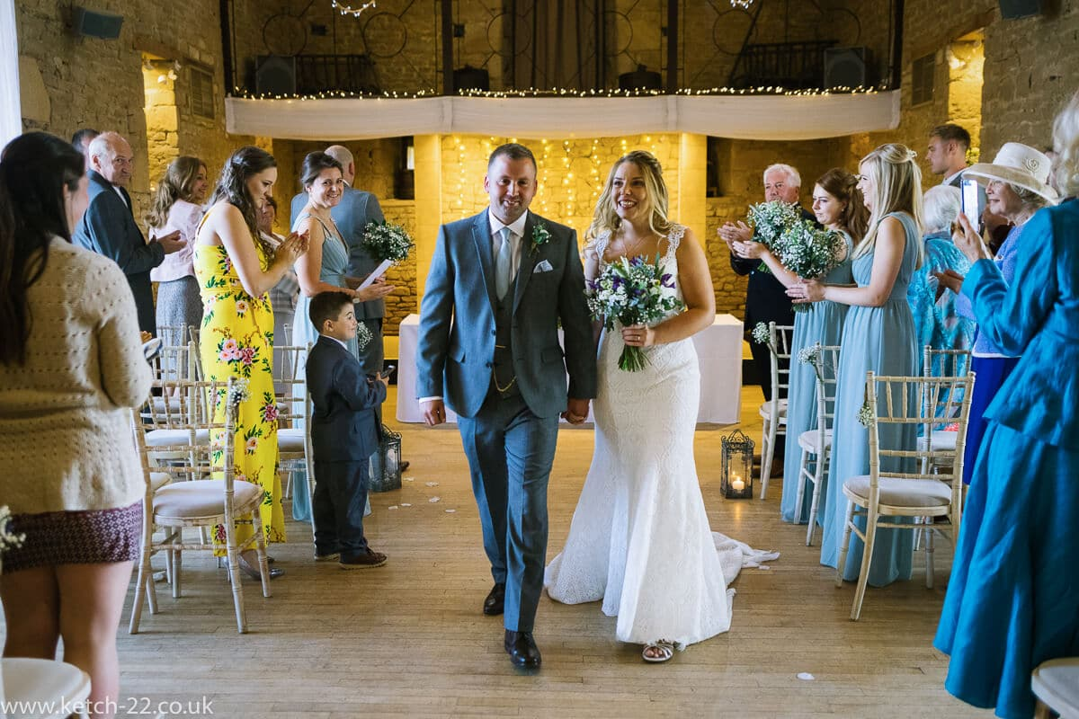 Bride and groom leaving ceremony at Wedding at The Great Tythe Barn