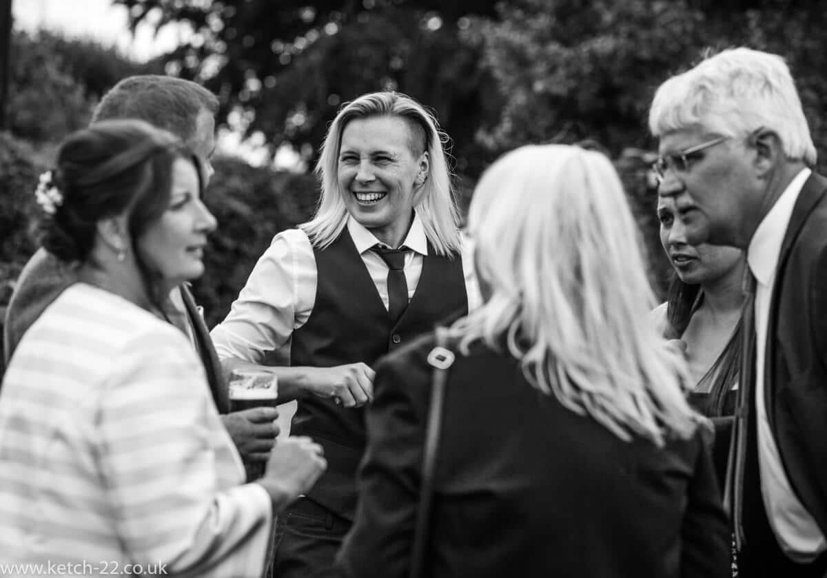 Black and white photo of wedding guests chatting