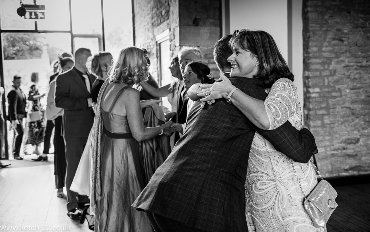 Mother of bride hugging wedding guests at The Great Tythe Barn