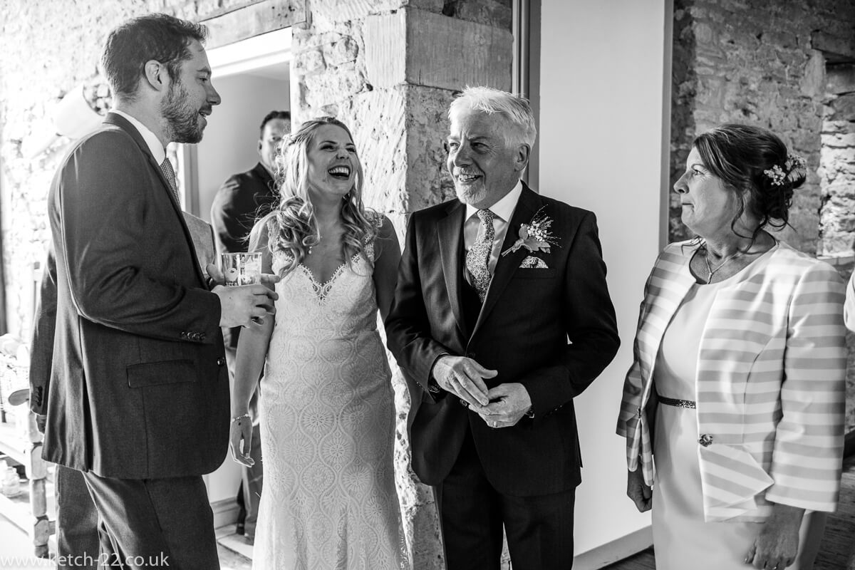 Father of bride laughing with daughter at wedding line up