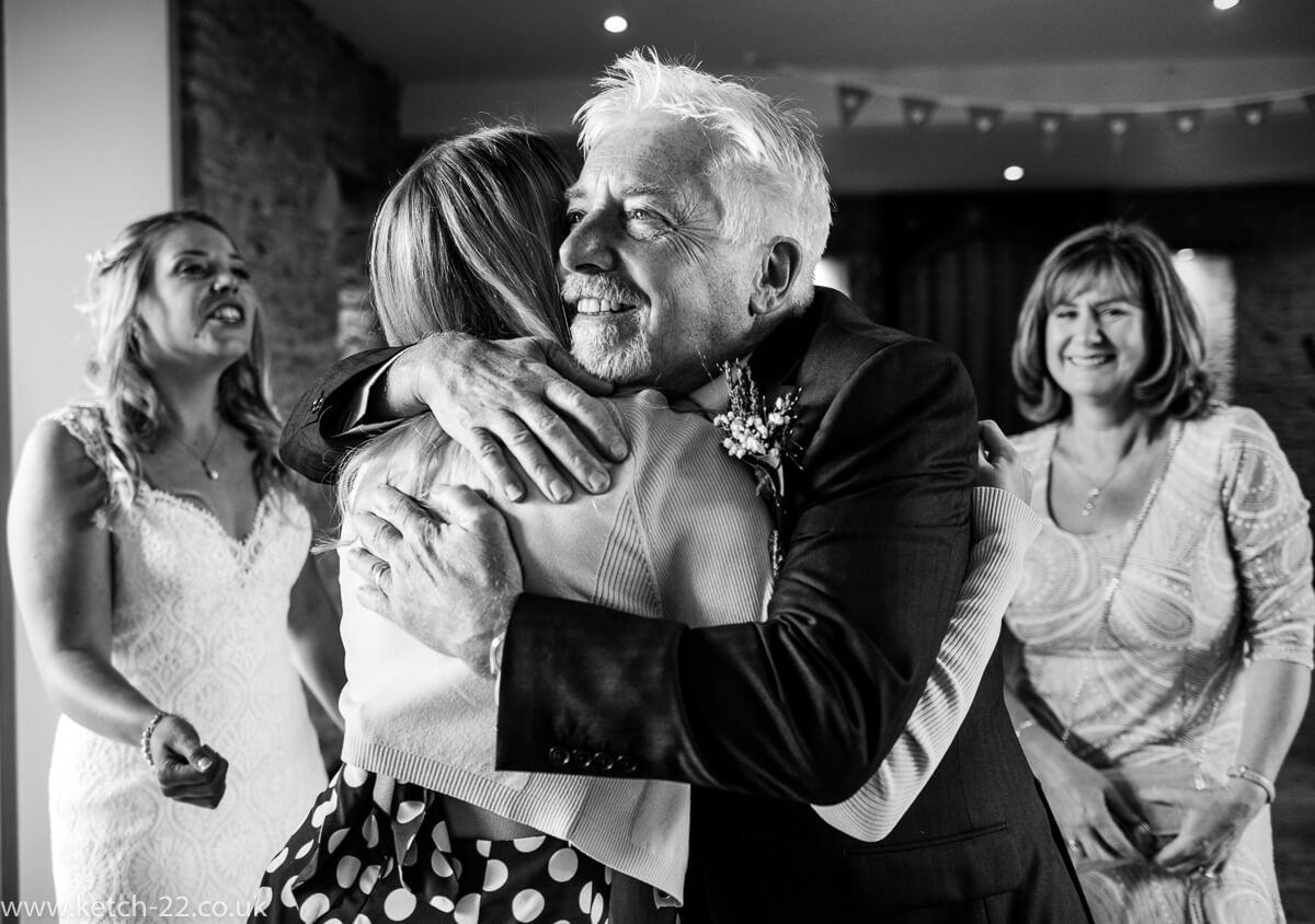 Wedding guest getting hug from father of bride