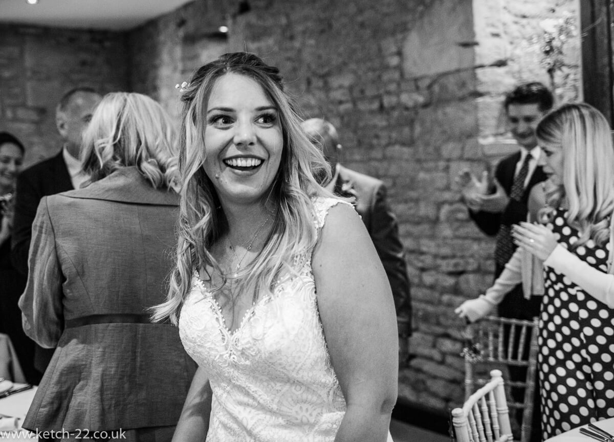 Happy bride enters dinning room at Weddings at The great Tythe Barn