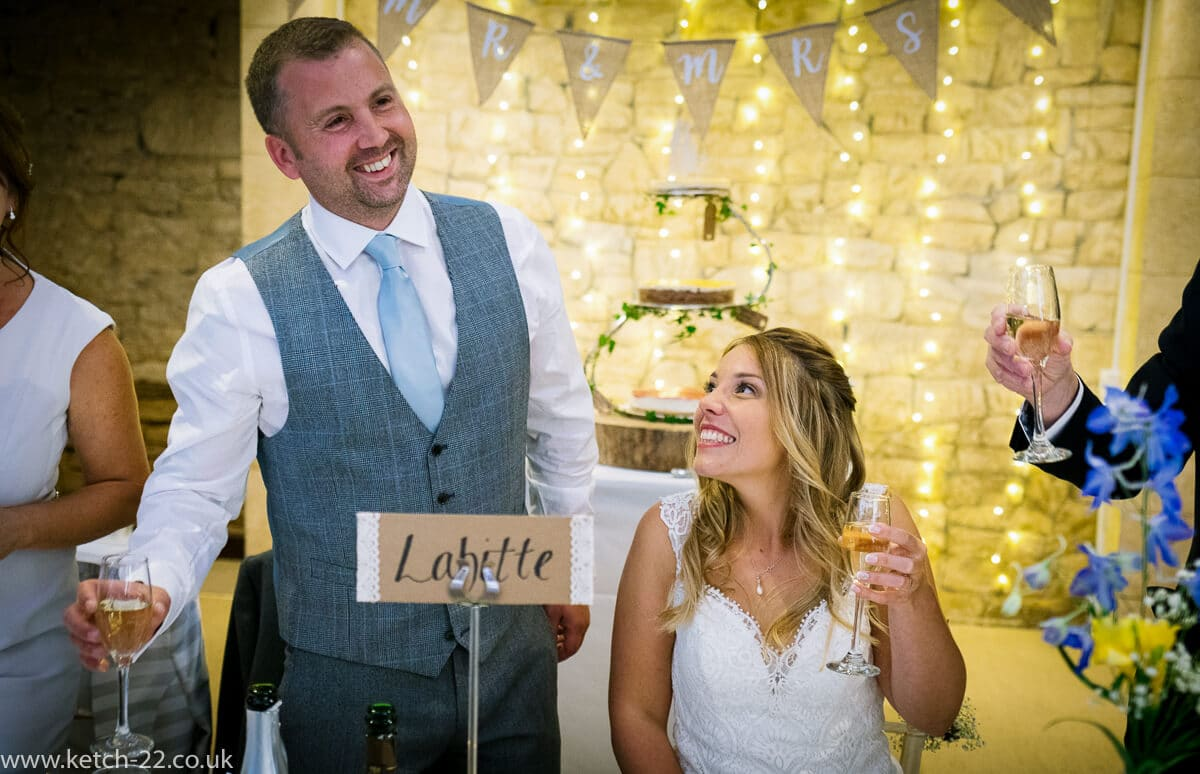Groom laughing as he makes speech at Wedding at The Great Tythe Barn