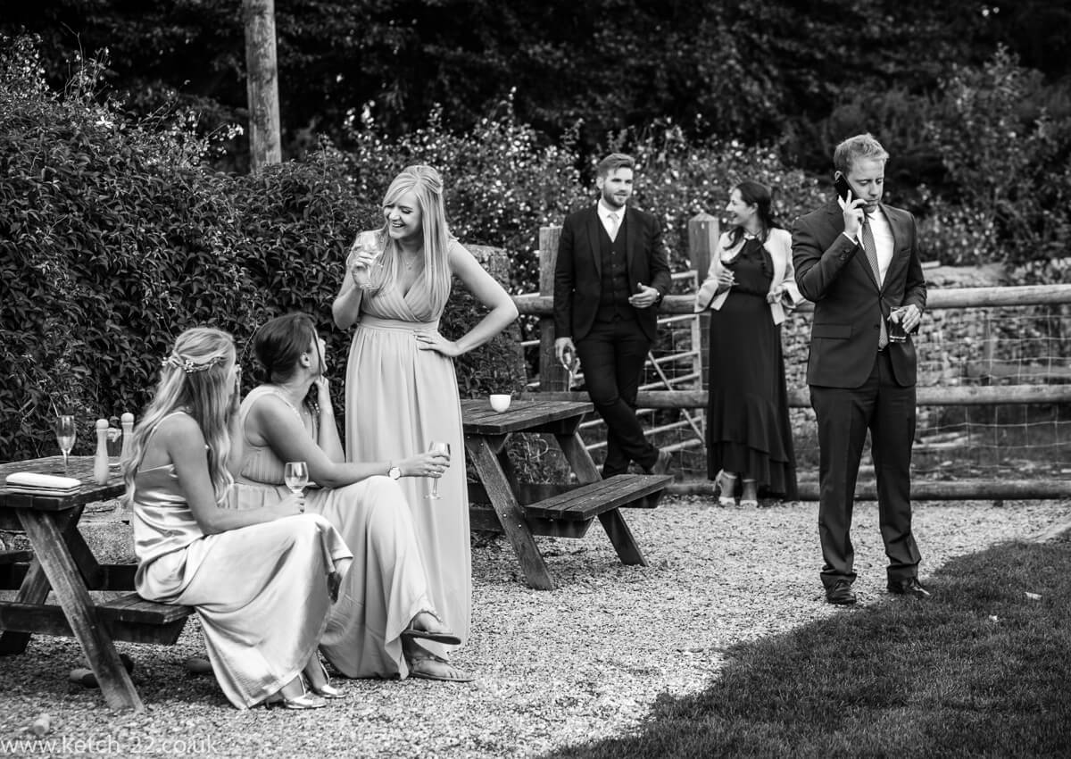 Bridesmaids chat on the lawn whilst wedding guest chats on the phone