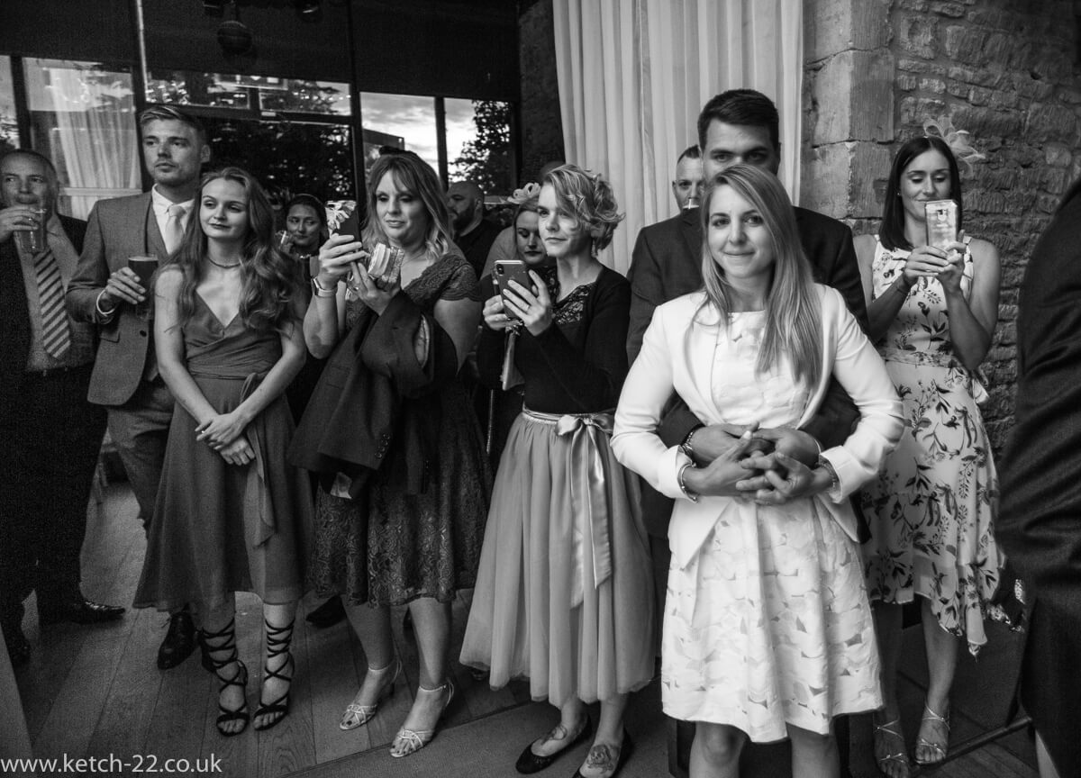 Wedding guests watching bride and groom take first dance