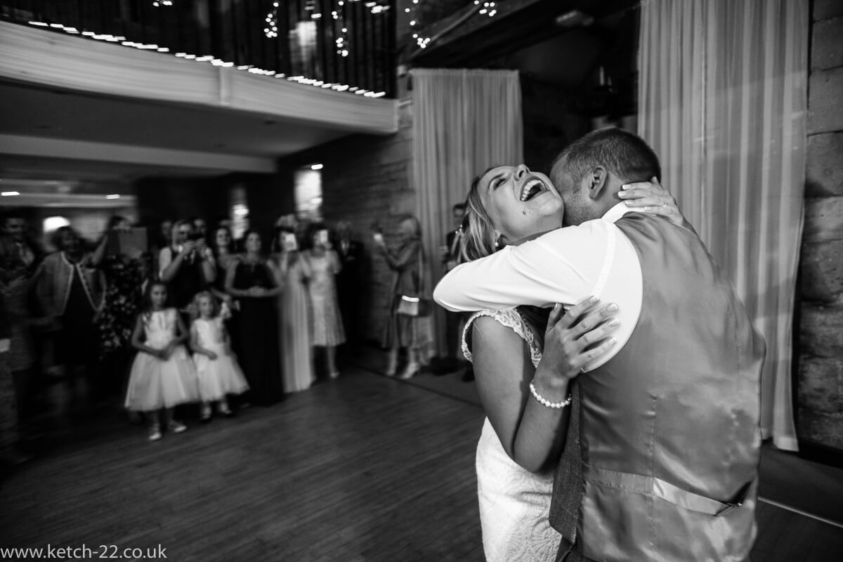 Laughing bride dancing with groom at the great Tythe Barn