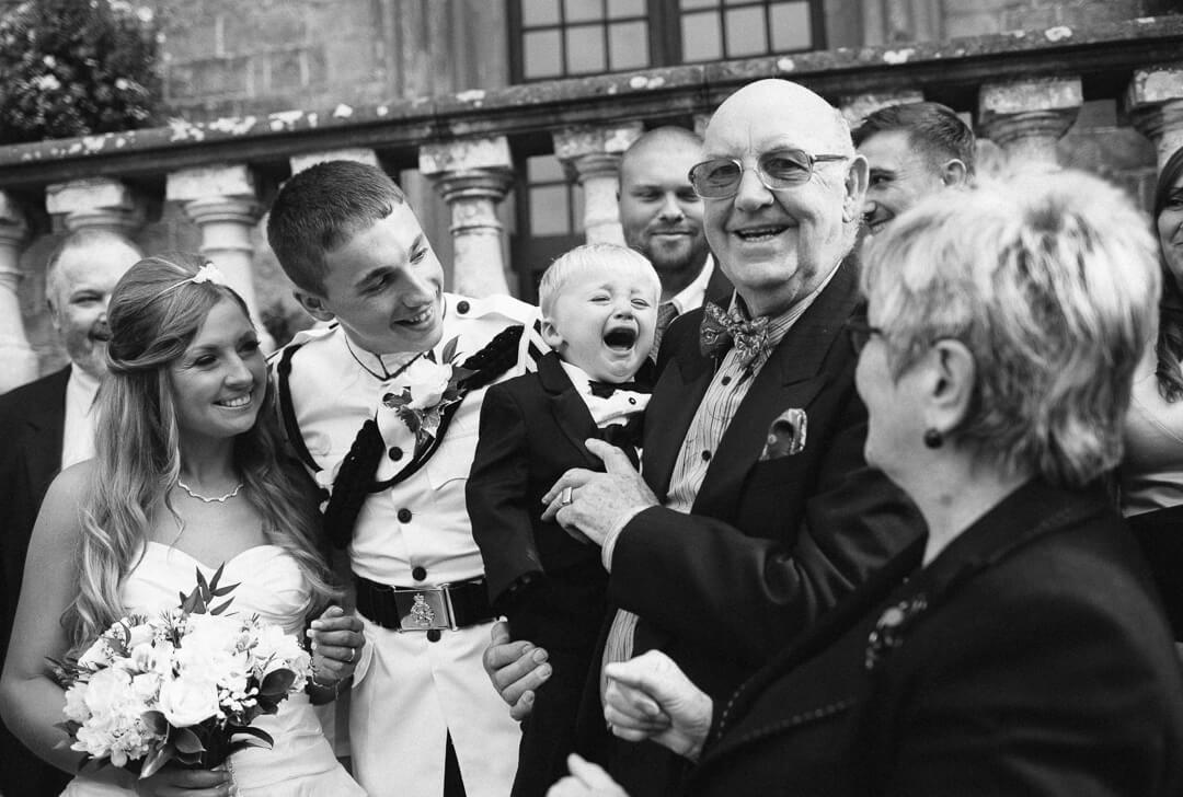 Page boy crying during family photos at wedding