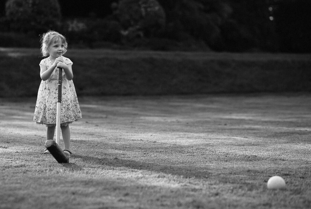 Little girl playing crouquet at Castle wedding