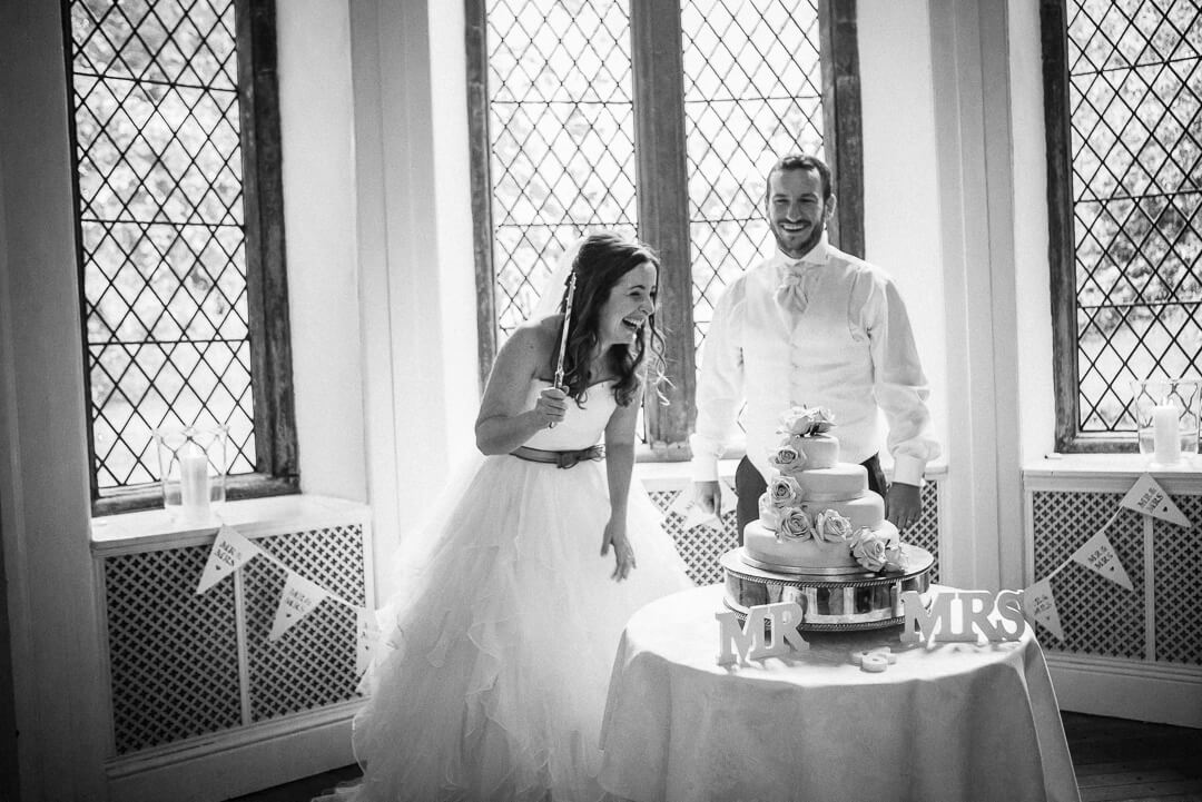 Quirky photo of bride and groom cutting the wedding cake