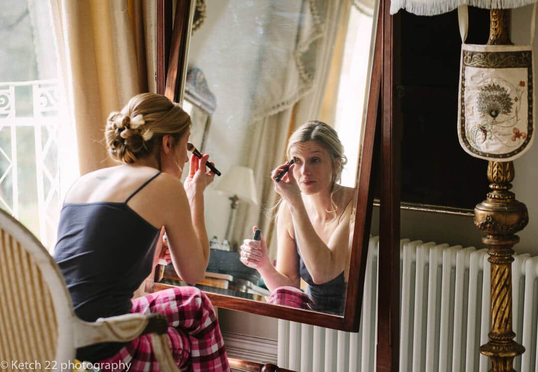 Bride putting make upon in mirror at Country House wedding