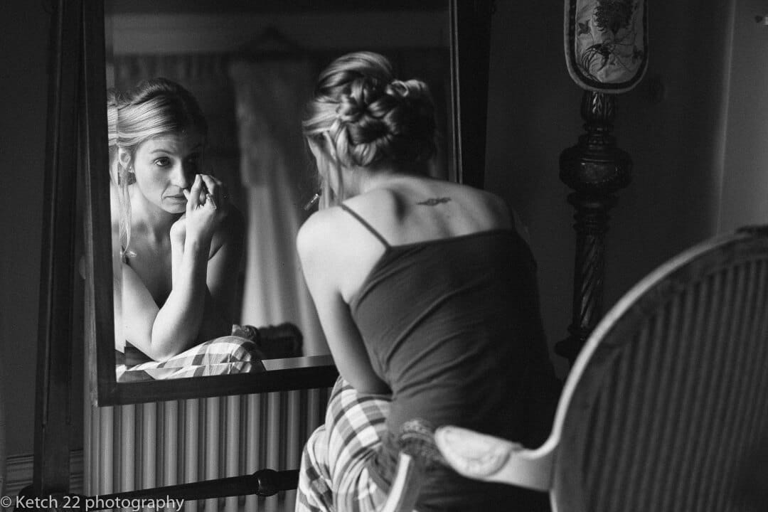 Documentary photo of bride putting make up on in mirror