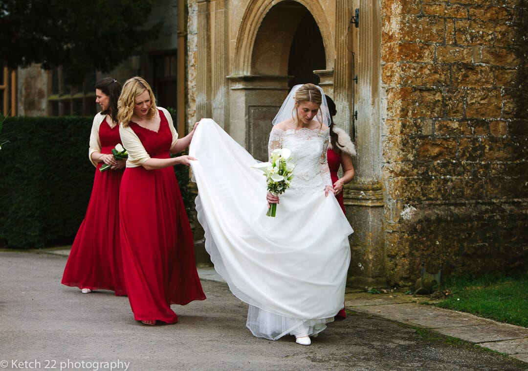 Bride walking with bridemaids in red dresses