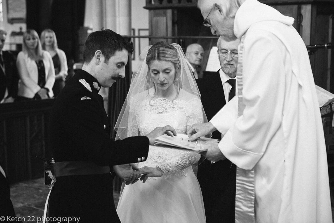 Bride and groom in army uniform exchanging wedding vows