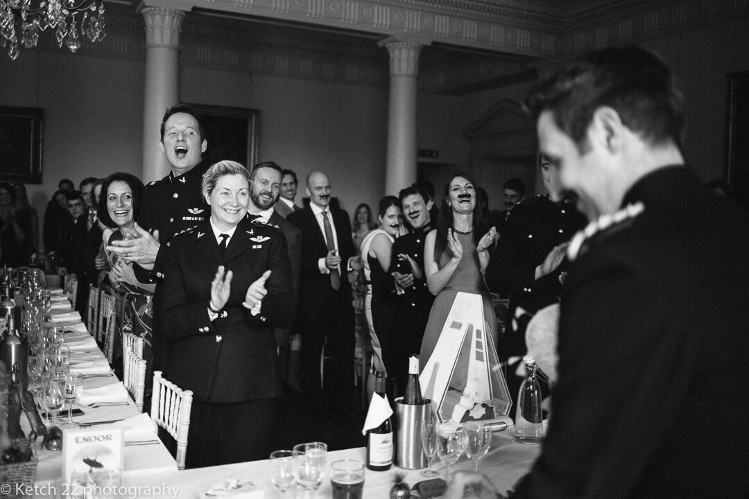 Wedding guests cheering bride and groom at Country house wedding