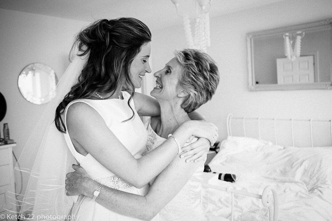 Mother hugging bride at wedding preparations
