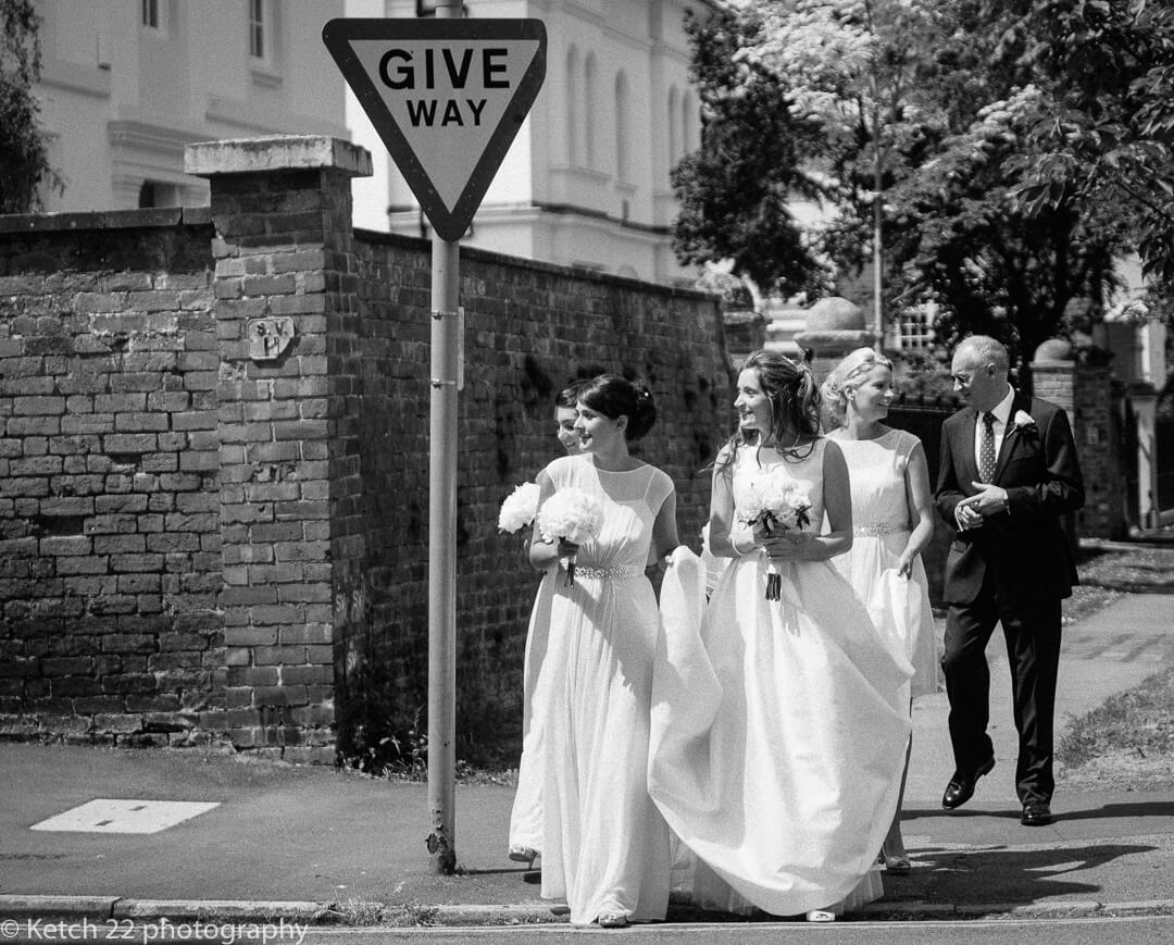 Bride and bridesmaids crossing the road at give way sign in Cheltenham