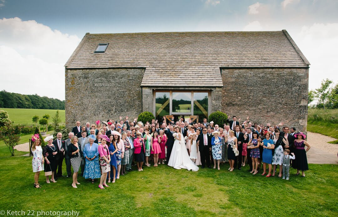Wedding party photo in front of Cripps Stone Barn in Gloucestershire