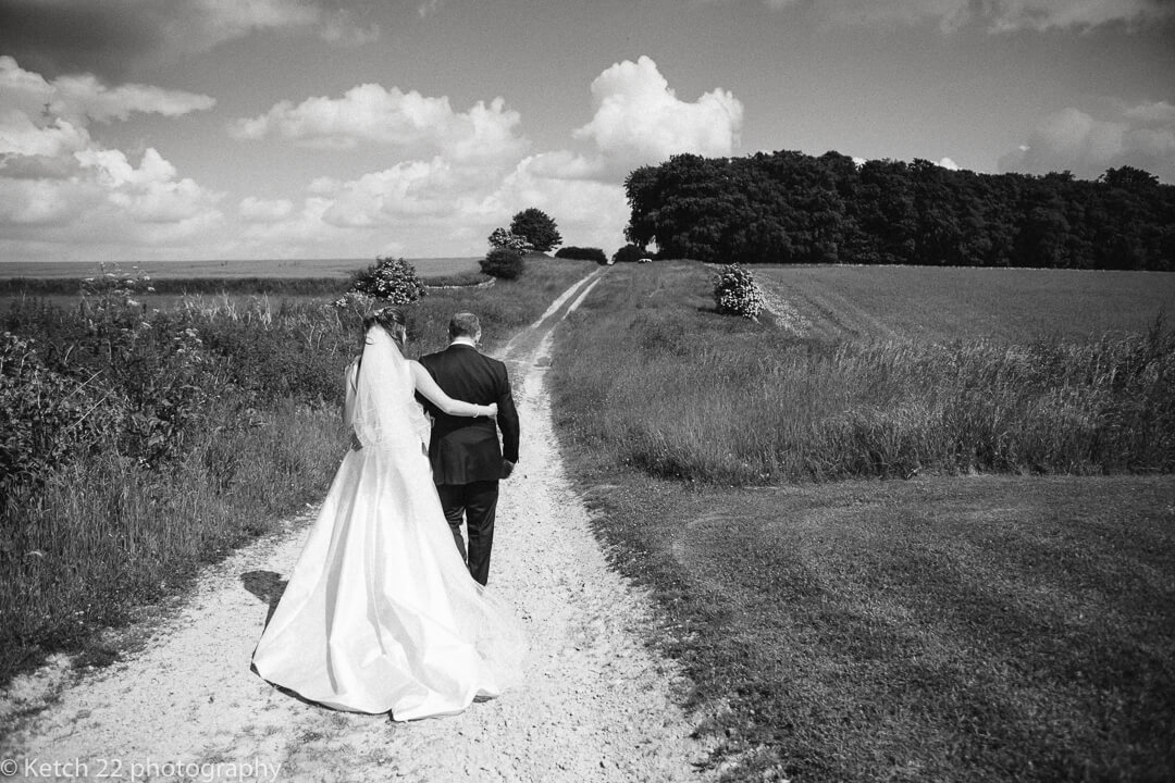 Bride and groom walk down country track at Cripps Stone barn wedding