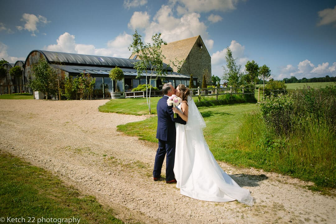 Bride and groom kissing in front of Cripps Stone Barn