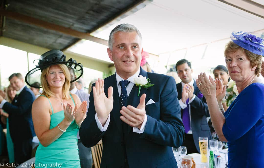 Wedding guests cheering as Newly weds enter dinning room