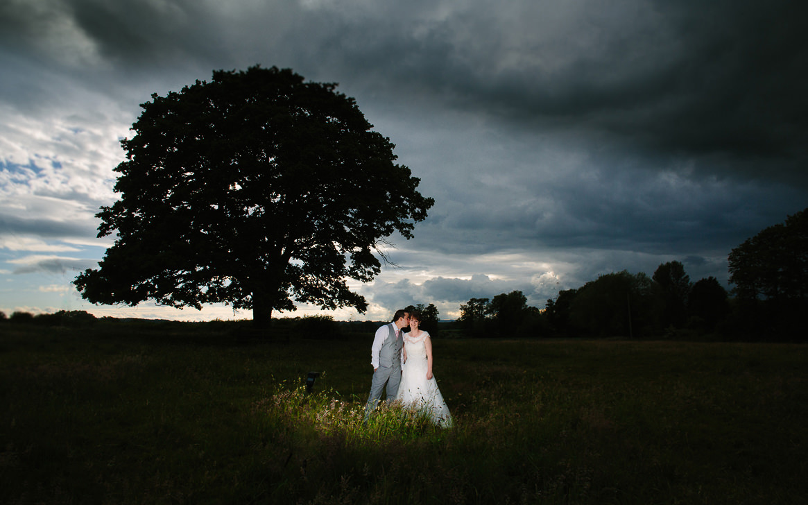 Bride and groom kissing in front of oak tree at Gloucestershire wedding