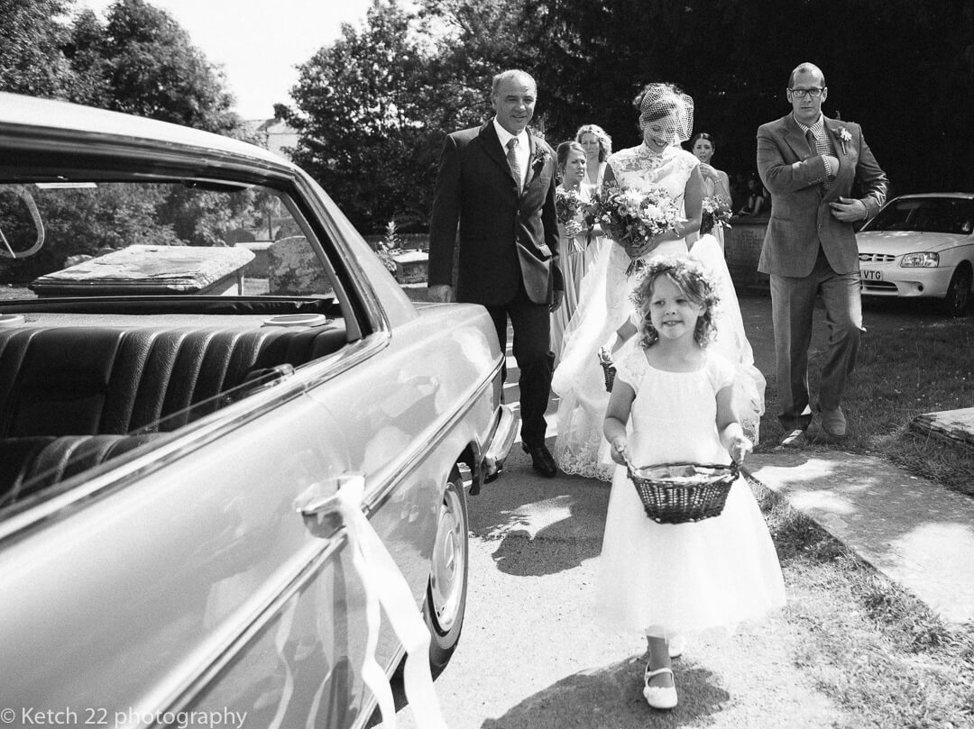 Flowere girl walking ahead of bride at Herefordshire wedding