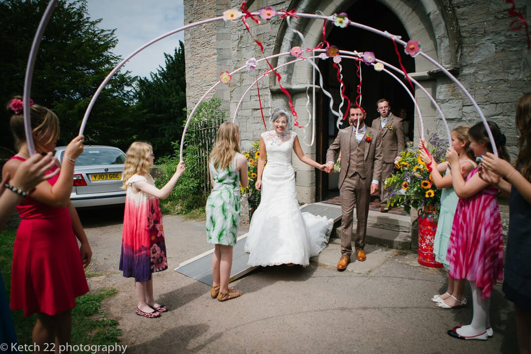 Bride and groom walking through colourful arch hoops after wedding ceremony