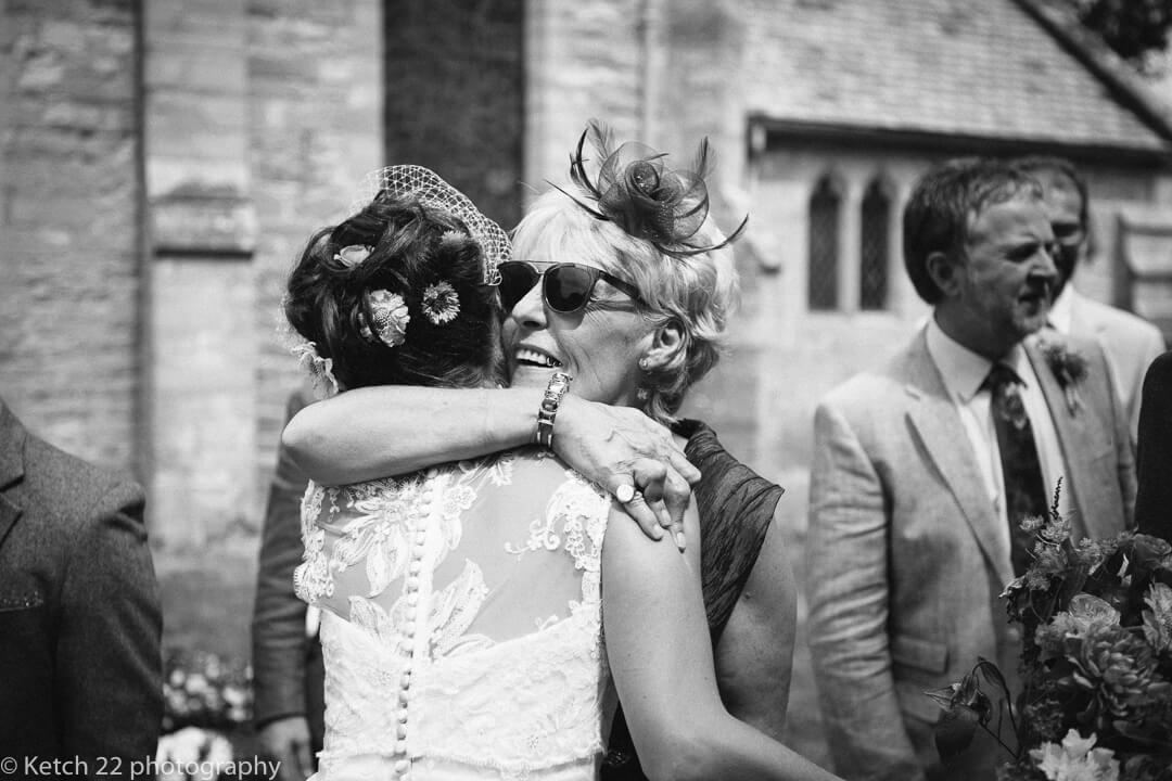 Wedding guest hugging bride at natural rural wedding