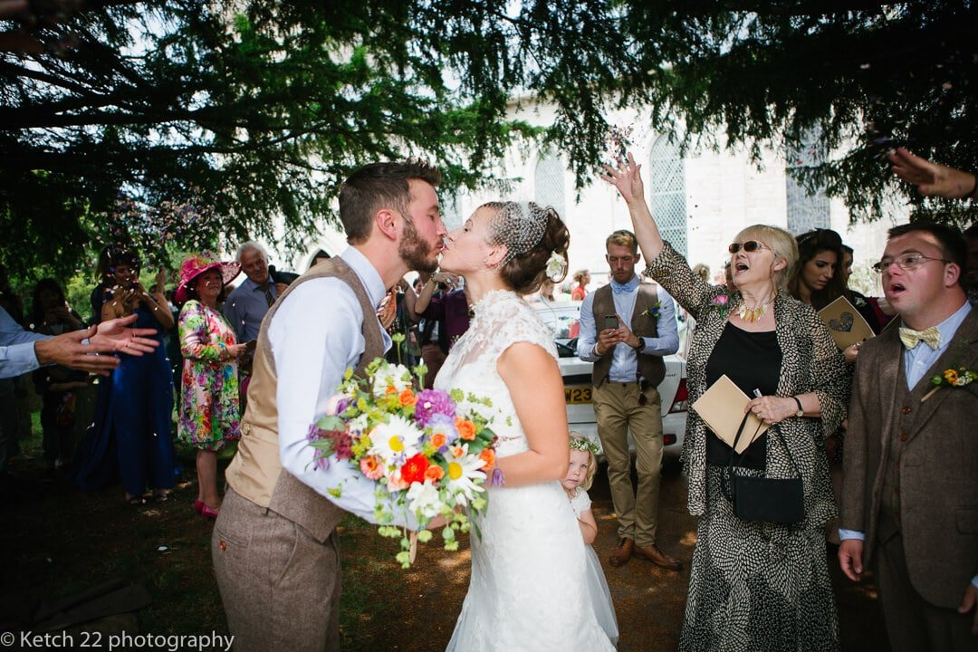 Bride and groom kissing outside church at rural wedding