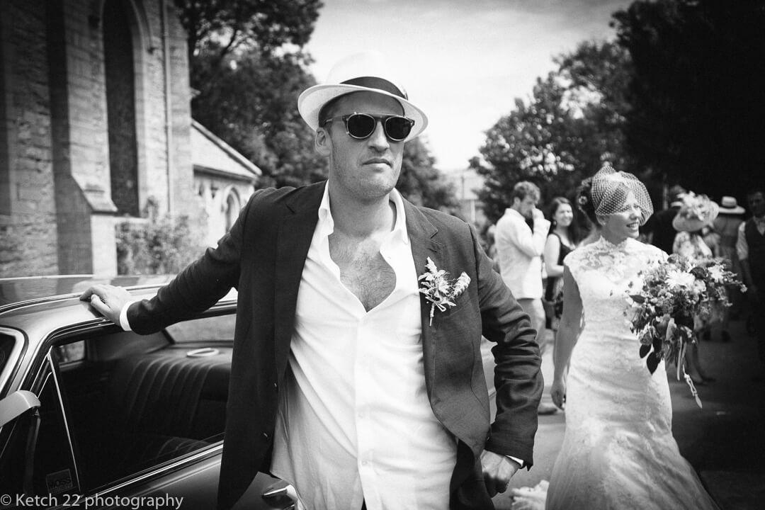 Best man waiting by wedding car at yurt wedding