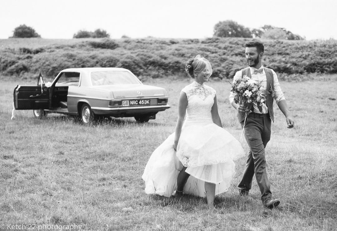 Bride and groom walk from wedding car at rural wedding in Herefordshire